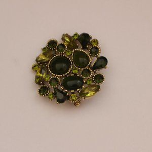 Green brooch with rhinestones and other stones.